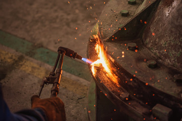 Metal cutting with acetylene and oxygen gas torch. Soft focus due to high ISO and shallow Depth Of Field.