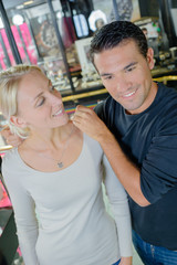 couple trying choising pearl necklace at jewelry store