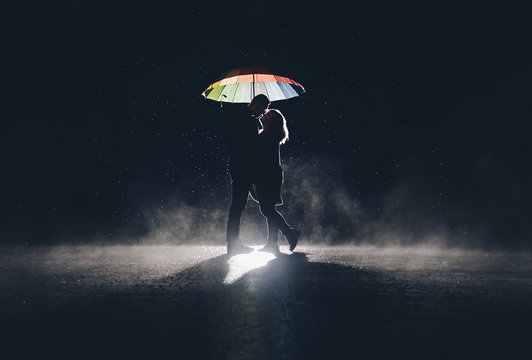 lovers under at colorful umbrella in the rain at night.