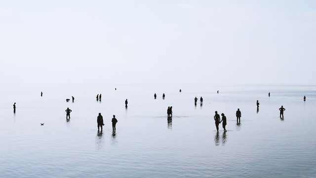 large group of people or crowd standing walking and swimming in shallow water at German north sea coast during ebb tide, backlit silhouettes