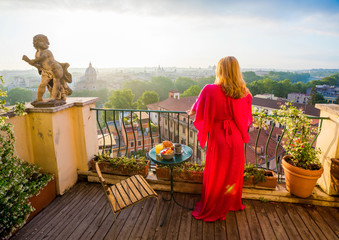 Woman standing on balcony and overlooking city in morning
