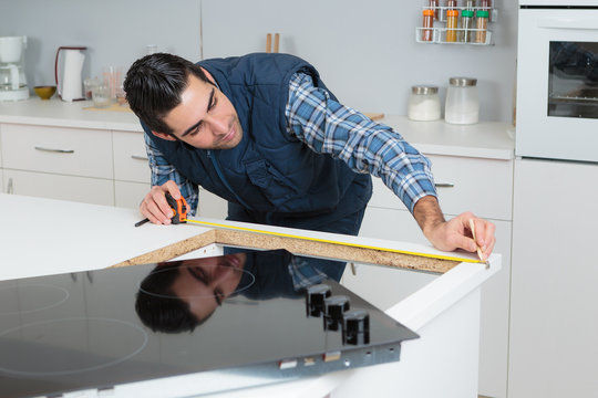 Man measuring worktop for installation of hob