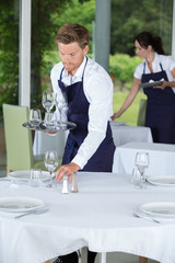 waiter setting a table at the restaurant