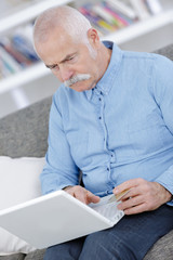 cute senior man with laptop at resort