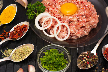 Minced meat. Ground meat with ingredients for cooking on a black background.