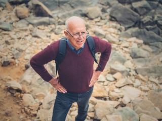 Senior man standing on rocks