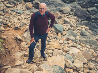 Senior man standing on rocks