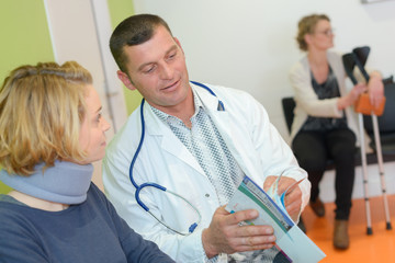 physiotherapist examining a female patients neck in clinic