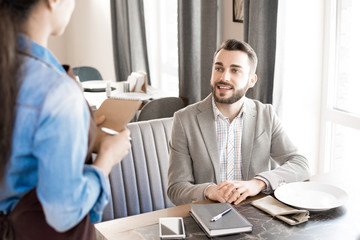 Cheerful handsome bearded young businessman in casual outfit smiling at waitress while making order and sitting at table with diary and smartphone in restaurant