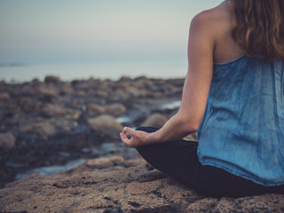 Young woman meditating on coast at sunset