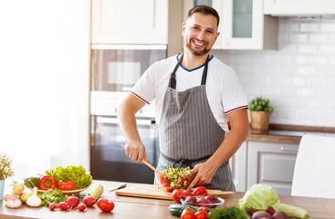 happy  man preparing vegetable salad in kitchen