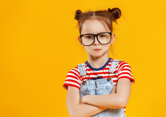 funny child girl in glasses on colored background