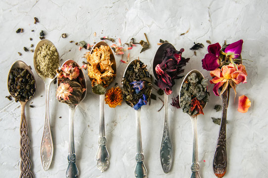 Assortment of dry green herbal and flower tea in a spoons on a white stone background.