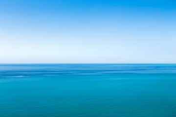 Beautiful blue unearthly seascape with clear sky and unusual stripes on the surface of the water