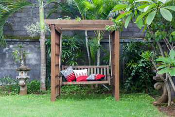 Classic outdoor wooden swing in the green garden with pillows