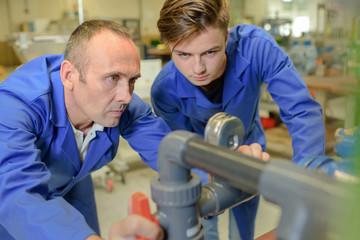 Two male engineers looking at pressure gauge
