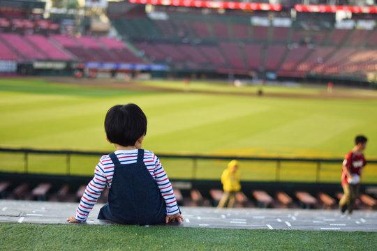 試合終了後の野球場で佇む男の子