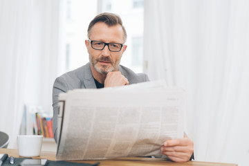 Middle-aged man immersed in reading the newspaper