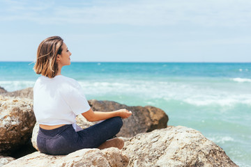Young woman meditating at the seaside