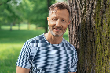 Casual middle-aged man leaning on a tree trunk