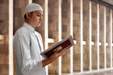 Muslim man reading koran in mosque