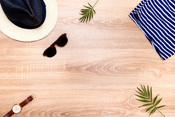 Top view of vacation accessories with copy space and summer beach items. Lay flat fashion background on wooden floor.