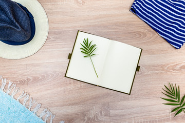 Top view of vacation accessories with blank notebook and summer beach items. Lay flat fashion background on wooden floor.