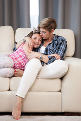 Cute teenage daughter in arms of her mother on the sofa