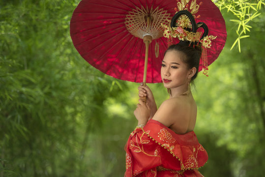 Chinese women in cultural costume holding umbrella in bamboo forest
