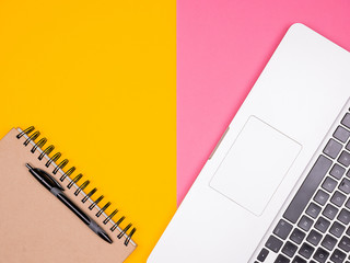 Paper notebook with a pen next to a laptop on two colored background. Pastel colors. Flat lay top view