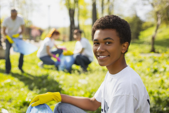 Rehabilitation of nature. Afro american male volunteer gazing at camera while collecting litter