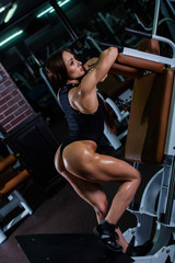 A muscular fitness woman with a very beautiful booty, in a black sexy body, resting in a Frank pose ha simulator for training legs. Dark gym.