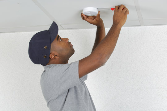 Man fitting smoke detector to ceiling