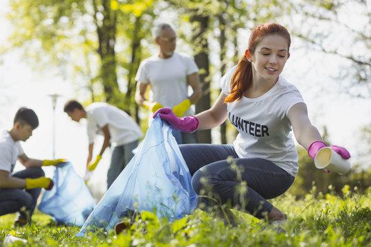 Volunteer program. Charming female volunteer gazing down while gathering rubbish