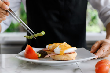 Concept picture, chef is preparing breakfast in hotel by put asparagus on egg benedict