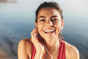 Close up of a happy sportswoman listening to music