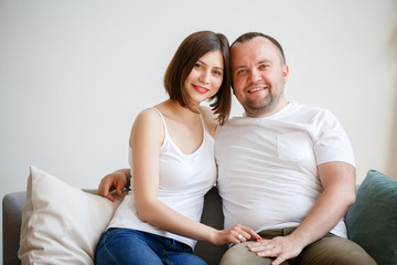 Photo of young married couple sitting on sofa