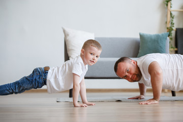 Image of happy dad and son pushing on floor