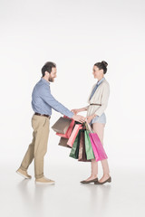 side view of smiling man taking shopping bags from wife isolated on white