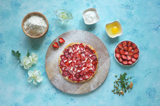 Strawberry pie. Ingredients for baking a strawberry pie on a turquoise kitchen table.