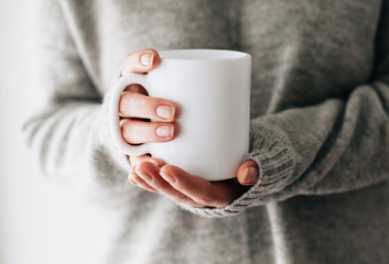 Printed roller blinds Tea Closeup of female hands with a mug of beverage. Beautiful girl in grey sweater holding cup of tea or coffee in the morning sunlight. Mug for your design. Empty.