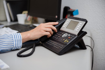 Closeup on busy office phone workplace, light table window. Modern administration control lcd display support solution response. Digital connection device communication landline equipment technology