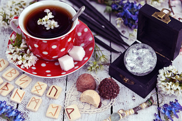 Cup of flower tea with runes, magic crystal and mystic objects with wildflowers. Occult, esoteric and divination still life. Halloween background with vintage objects