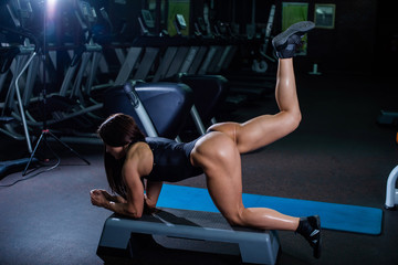 A muscular fitness woman with a very beautiful booty, in a black sexy body, raises her leg back, standing on the fours. Dark gym