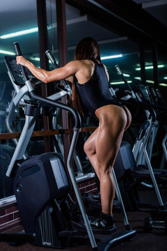 A muscular fitness woman with a very beautiful booty, in a black sexy body, trains on the stair-stepping machine. Dark gym.