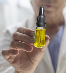 Doctor offering CBD oil bottle to patient