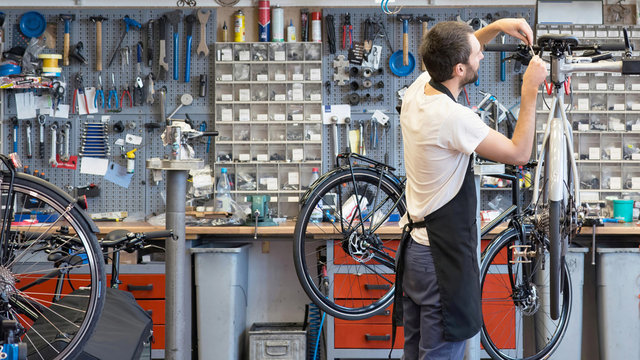 friendly and competent bicycle mechanic in a workshop repairs a bike