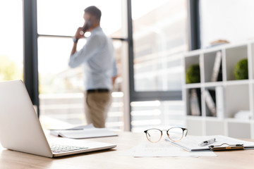 Photo closeup of workplace with office stuff lying on table, while defocused business man speaking on smartphone and looking through big window