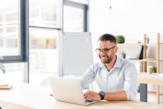 Photo of joyous office man 30s in white shirt sitting at desk and working on laptop in business centre