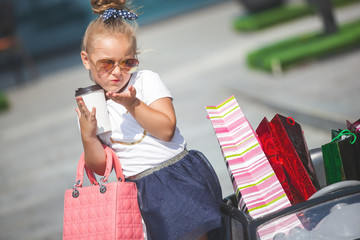 Pretty little girl fashionista making shopping with shopping bags. Cute child outdoors in the toy car